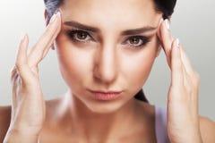 Mal de tête intense La fille tient sa tête dans des deux mains migraine Le concept de la santé sur un fond gris photographie stock libre de droits