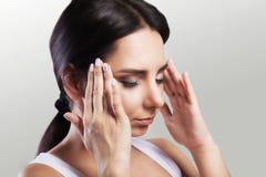 Mal de tête intense La fille tient sa tête dans des deux mains migraine Le concept de la santé sur un fond gris images stock