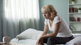 Mal de tête se sentant femelle en difficulté, se reposant sur le lit, attaque de migraine, malaise d'effort image libre de droits