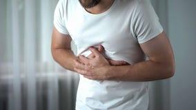 Mal di stomaco ritenente maschio a casa, sintomo di gastrite, ulcera peptica, pancreatite fotografia stock