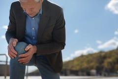 Mal vieillissant de genou de sentiment de retraité dans la rue Image libre de droits