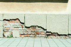 Mala base de la fundación en casa vieja o pared agrietada constructiva de la fachada del yeso con el fondo del ladrillo imagenes de archivo