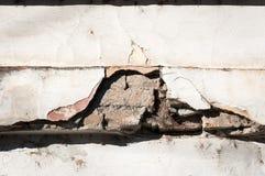 Mala base de la fundación en casa vieja o pared agrietada constructiva de la fachada del yeso con el fondo del ladrillo imagen de archivo libre de regalías