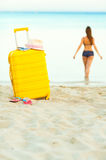 A mala de viagem amarela na praia e em uma menina anda no mar no th Imagem de Stock Royalty Free