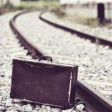 Mala de viagem ao lado das trilhas de estrada de ferro imagem de stock