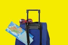 Mala de viagem azul com os acessórios do viajante no fundo brilhante azul Estilo mínimo fotografia de stock