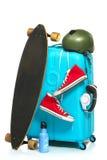 A mala de viagem azul, sapatilhas, skate no fundo branco fotografia de stock royalty free