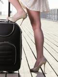 Mala de viagem da amarração do mar do pé da menina da mulher em um cais Fotografia de Stock Royalty Free