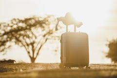 Mala de viagem e chapéu com por do sol do fundo foto de stock