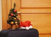 Mala de viagem e chapéu de Santa de encontro a uma porta de madeira. Foto de Stock Royalty Free