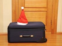 Mala de viagem e chapéu de Santa de encontro a uma porta de madeira. Fotografia de Stock