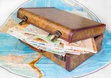 Mala de viagem e mapas no fundo branco Foto de Stock