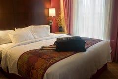 Mala de viagem na cama do hotel Imagem de Stock