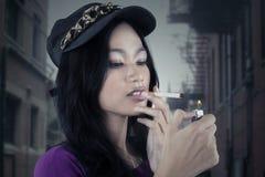 Mala muchacha que se enciende encima de un cigarrillo Imagen de archivo