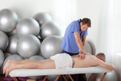 Mala postura del masajista durante masaje Imágenes de archivo libres de regalías