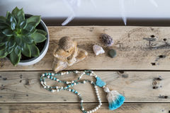 Mala and wooden buddha. Peaceful tabletop scene with wooden Buddha statue, mala beads, dreamcatcher and plant Stock Images