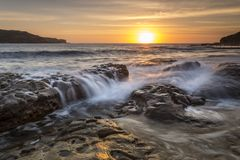 Malabar Long Bay Sunrise Sydney Australia. Sun rising on the horizon shining its golden light down Long Bay to Malabar with rock flows in the foreground royalty free stock photography