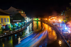 Malacca city center at night. Blurred touristic boat going by the channel in Historical part of the old malaysian town Malacca, Malaysia at night. It is listed stock photos