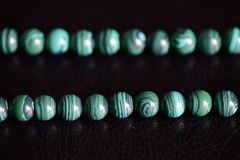 Malachite η πέτρα διακοσμεί το περιδέραιο σε ένα σκοτεινό υπόβαθρο με χάντρες στοκ εικόνες