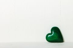 Malachite heart. Green malachite heart on wooden background, painted white color Royalty Free Stock Photo