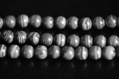 Malachite stone beads necklace on a dark background. Black and white. Malachite stone beads necklace on a dark background close up. Black and white royalty free stock images