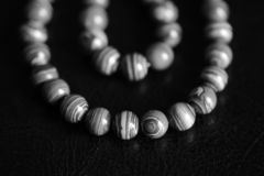 Malachite stone beads necklace on a dark background. Black and white stock photo