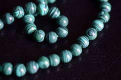Malachite stone beads necklace on a dark background. Close up royalty free stock images