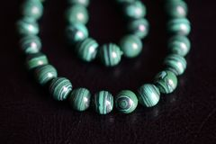 Malachite stone beads necklace on a dark background stock photos