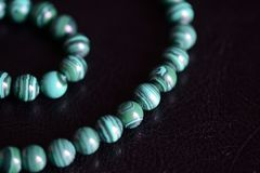 Malachite stone beads necklace on a dark background. Close up stock images