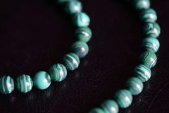 Malachite stone beads necklace on a dark background. Close up royalty free stock photo