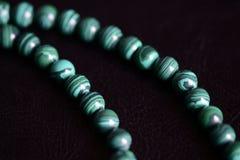 Malachite stone beads necklace on a dark background. Close up royalty free stock image