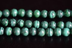 Malachite stone beads necklace on a dark background stock image