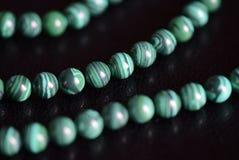Malachite stone beads necklace on a dark background. Close up stock photos