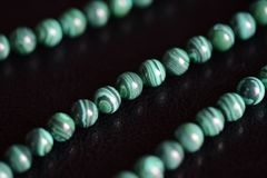 Malachite stone beads necklace on a dark background stock photo