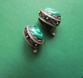 Malachite stud earrings. Against green background royalty free stock image