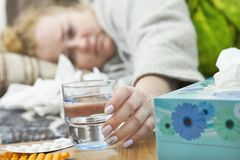 Malade de jeune femme dans le lit tenant un verre de l'eau Photo stock