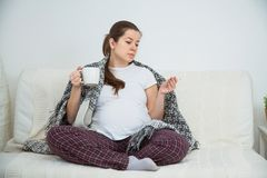 Malade de sensation de femme enceinte de jeunes, grosse fièvre, se reposant sur le sofa à l'intérieur images stock