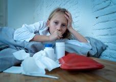 Malade menteur de petite fille dans le lit toussant le sentiment en difficulté avec la grosse fièvre ayant une grippe froide photographie stock libre de droits