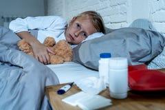 Malade menteur de petite fille dans le lit vérifiant le sentiment de thermomètre en difficulté avec la grosse fièvre ayant une gr image stock