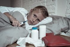 Malade menteur de petite fille dans le lit vérifiant le sentiment de thermomètre en difficulté avec la grosse fièvre ayant une gr photos libres de droits