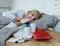 Malade menteuse de petite fille dans le lit soufflant son sentiment de nez en difficulté avec la grosse fièvre ayant une grippe f image libre de droits