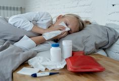Malade menteuse de petite fille dans le lit soufflant son sentiment de nez en difficulté avec la grosse fièvre ayant une grippe f photographie stock libre de droits