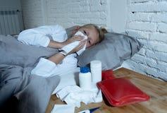 Malade menteuse de petite fille dans le lit soufflant son sentiment de nez en difficulté avec la grosse fièvre ayant une grippe f photos libres de droits