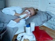 Malade menteuse de petite fille dans le lit soufflant son sentiment de nez en difficulté avec la grosse fièvre ayant une grippe f photographie stock