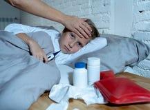 Malade menteuse de petite fille dans le sentiment de lit en difficulté ayant des symptômes froids d'une grippe et sa température  photo stock