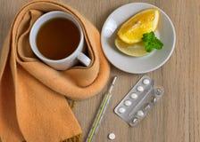 Maladie de concept, froids, traitement Tasse de thé, de thermomètre, de pilules et d'une écharpe tricotée Vue supérieure Photographie stock libre de droits