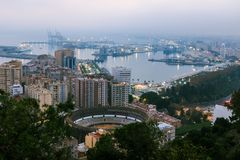 Malaga Cityscape in the evening with bull arena and trees stock images