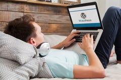 MALAGA, ESPANHA - 10 DE NOVEMBRO DE 2015: Logotipo do tipo de Wordpress no tela de computador Homem que datilografa no teclado