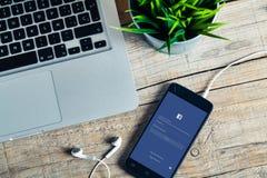 MALAGA, ESPANHA - 29 DE OUTUBRO DE 2015: Facebook app em um telefone celular, perto de um portátil, sobre uma mesa de madeira , Imagens de Stock
