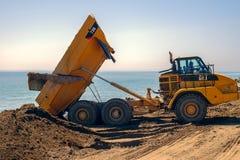 Large trucks restore sand on the coast expanding the beach. Malaga, Spain - April 17, 2018. Large trucks restore sand on the coast expanding the beach Huelin Royalty Free Stock Photo